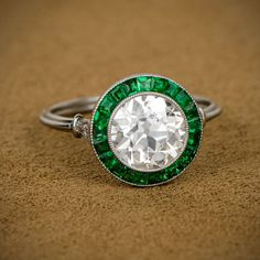 A beautiful old european cut diamond, surrounded by a stunning halo of French-cut emeralds. Sold by Estate Diamond Jewelry