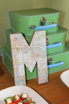 Birthday Child 1st name letter in mapped papers. & suitcases as props