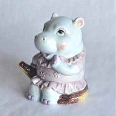<p>Tirelire hippopotame vintage en porcelaine bleue pale en forme d'hippopotame femelle assise sur un crocodile, fente dans le dos et bouchon en plastique sous la base, état d'usage, quelques petits éclats. Pour économiser et s'offrir de belles vacances ou faire le cadeau le plus kitch du moment! - deco-graphic.com