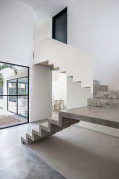 U-shaped concrete staircase. Casa Garcias by Warm Architects. Photo by Wacho Espinosa Photography.
