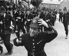Comedian Norman Wisdom dressed as a policeman running through the streets with a large group of policemen filming 'On the Beat' in Windsor England...