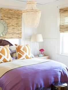 Bedroom makeover: Earthy Escape - Pair vibrant purple with natural elements like bamboo shades and a beaded chandelier to create a peaceful oasis. Unique throw pillows reiterate the brown tones, and an old glass jug finds new life as a charming bedside lamp.