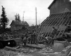 Le 11 juillet 1944 à l'ouest de Saint-Fromond au nord de Saint-Lô, des Engineers récupèrent des décombres (briques et tuiles) d'un mur sous une toiture détruite, dans la benne d'un GMC CCKW 353 LWB benne Génie de la C Co, unité ? (immatriculation caviardée) unité du Génie US.  Il s'agit de récupérer des matériaux pour réparer les routes