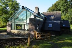 Structurally Glazed extension with glass gable and glass roof set against a stone barn conversion