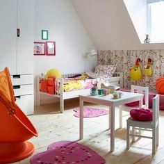 Farebná detská izba s bielou posteľou a farebnými posteľnými obliečkami. Na obrázku s ružovými kobercami, detským otočným kreslom s krytom a bielym stolom s dvoma stoličkami.
