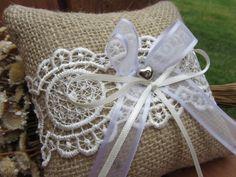 Almofada artesanal rústica para alianças. Confeccionada com juta, renda cor pérola com detalhes em lantejoulas transparentes, fitas de cetim branca e pérola e coração com strass.