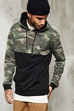 A French terry knit hoodie with a camo print paneled top half, a drawstring hood, long sleeves, ribbed trim, and a kangaroo pocket.