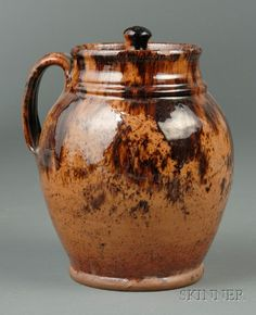 Covered Redware Handled Jar, America, early 19th century, ovoid form with molded bands about the neck, streaked and speckled brown manganese glaze, (chips), ht. 8 1/4 in.          cover with several chips, small to 3/4 x 1/2 in., three small shallow rim chips and a few glaze flakes around rim, some surface scratches around bulbous area of body.  Sold for $ 3,555