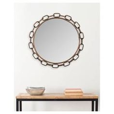 "Add an industrial chic twist to your home interior with the Safavieh Atlantis Chainlink Wall Mirror. This eye-catching accent piece will be a cool addition to your foyer, bedroom, bathroom, living room or hallway with its chain-inspired circular frame and crystal clear mirror glass. Featuring a glass, iron and wood construction, wall mounting bracket and an antiqued bronze-toned frame. Dimensions measure 29""x29""x2"". Use glass cleaner on the Atlantis Chainlink mirror su..."