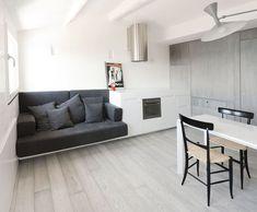 35MQ CAMOGLI_La zona giorno dell'appartamento con il mobile che accoglie divano e cucina. Gli arredi sono stati realizzati su misura per sfruttare al meglio la superficie ridotta. Dietro al tavolo si intravede il volume di legno grigio che contiene la camera matrimoniale