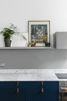 Art in a dark blue / grey marble kitchen in a Swedish space. Entrance.