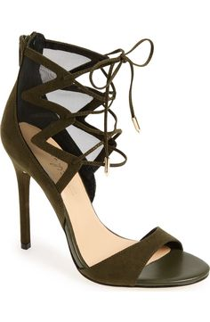 Swooning over these gorgeous olive and black suede shoes! Ghillie-style lacing and a mesh ankle cage sit atop a towering wrapped stiletto in this leg-lengthening sandal.