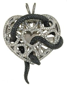 For you snake lovers out there...An 18ct white gold diamond and coloured diamond pendant, by Theo Fennell  Modelled as a pavé black diamond serpent entwined within a brilliant-cut diamond-set openwork heart, mounted in 18ct white gold, 6.6cm long, black diamonds not tested for natural colour origin, London hallmark  Signed Fennell