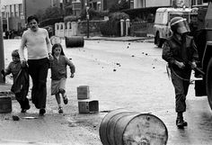 A father walking past soldiers during a riot with his children in Belfast, 1979