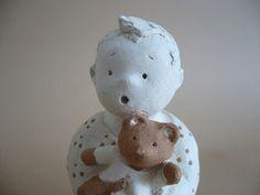 Figurine décorative sculptée en terre cuite blanche et quelques touches rose orangé.  Petit garçon assis, tenant serré contre lui son doudou, un ours brun, habillé d'un gile - 7459445