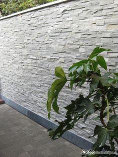 Terraszijde leistenen muur: Strips van natuursteen, type Grijs Kwartsiet, verwerkt op een tuinmuur.