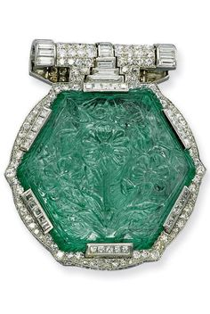 AN ART DECO EMERALD, DIAMOND AND MOTHER-OF-PEARL BROOCH, CIRCA 1925. The central Moghul hexagonal carved emerald, 19th century, set within a single and square-cut diamond frame to the similarly-set surmount and inlaid mother-of-pearl clip reverse, mounted in platinum, 5.6 cm long. #ArtDeco #brooch