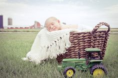 newborn photo with john deere tractor.. so cute.. hopefully something like this for her pics!!