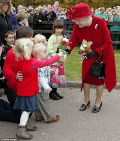 In 2009, pictured, Her Majesty added contrast to the blaze of red to greet wellwishers in ...