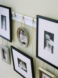 family photo gallery hanging on rail with chain...could also use ribbon or twine