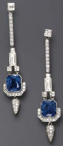 A PAIR OF DIAMOND AND SAPPHIRE EAR PENDANTS. Each square-cut diamond, suspending a circular-cut diamond line, to the square and baguette-cut diamond link, terminating in a rectangular-cut sapphire, weighing approximately 4.91 and 4.59 carats, enhanced by circular-cut diamond trim and a pavé-set diamond drop, mounted in platinum, in a red leather case.