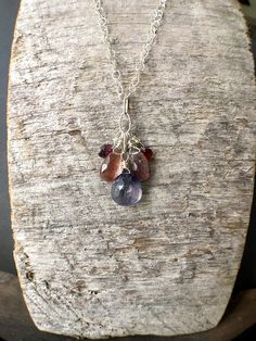 A necklace in jewel tones. This necklace features a faceted iolite briolette that is surrounded by faceted moss amethyst briolettes and smaller faceted briolettes of tourmaline and garnet. The briolettes are wrapped in sterling silver and attached to sterling silver chain. The