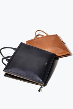 isaac mizrahi new york: chic tan and black leather laptop or tablet cases which also function as square briefcases. Could use it as a minimalist tote as well #leatherbags