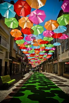 "Beautiful art installation in Agueda, Portugal. ~~~ ""I love the way light plays through translucent materials & jewel tones are my favorite! The natural light shining through these colorful umbrellas provide a jeweled toned sky above & whimsical shadow play below.  This provides much needed shade & a mood booster all in one!"" ...photographer Diana Tavares"
