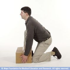Photo of man kneeling to lift a box