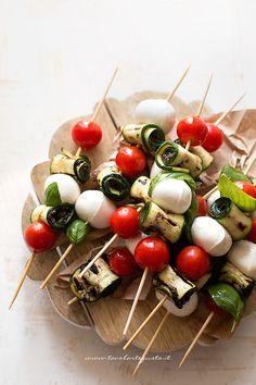 Gli Spiedini di zucchine sono un goloso finger food fresco ed estivo, realizzato con zucchine grigliate farcite con patè di olive nere, pomodorini, bocconcini di mozzarella e foglie di basilico. Un pi