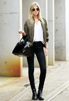 A white t-shirt is worn with a green bomber jacket, black skinny jeans, black boots, a black leather bag, and black sunglasses