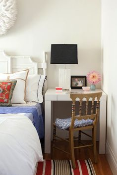 Fun bedroom with white juju hat over white bamboo headboard accented with colorful pillows over striped rug next to West Elm Parsons Mini Desk - White used as nightstand filled with white faux bois lamp paired with wood chair.