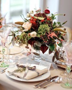 Set your reception tables in red, white, and green bountiful arrangements of ranunculus, roses, grasses, and berries for a December wedding.