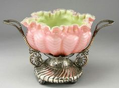"""A Stevens Williams cased satin glass centerpiece, the bowl having a green glass interior, the exterior in pink undulating herring bone pattern with ruffled rim mounted upon an elaborate silver plate pedestal with gadrooned swirls leading to a central column with chased flowers to which rope-twist handles and fern fiddle supports are applied; the glass unmarked, the base marked, """"Simpson, Hall, Miller Wallingford Ct."""" 9.5""""H, Circa - 1880 - 1920."""