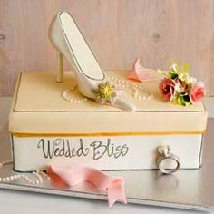 Bridal shower cake that looks just like a shoe box. It's obvious that the brides loves the finer things in life. Decorated with a fondant engagement ring, white pearls and pink fondant ribbon. And a shoe bridal shower cake topper. From www.thecakegirls.com