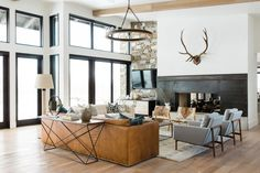 The steel fireplace surrounds add industrial edge to the living area, while antlers found on Craigslist were mounted to give a nod to the rustic surroundings. The chandelier is by Ralph Lauren Home, the leather sofa is by RH, and the rug is from McGee & Co.