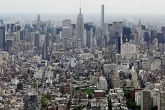 Midtown Manhattan, including the Empire State Building, center, are seen from the observatory at One World Trade Center in New York.