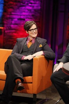 Australian comedian Hannah Gadsby.  Did she know the couch would be orange?