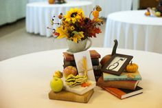 """Autumn Wedding Reception Centerpieces: Stacks of books (free from """"the Book Thing"""" in Baltimore, which we ended up returning once it was all over (some were from my personal collection), large tea cups filled with sunflowers and leaves, and gourds and apples from the local farmer's stand, which we ended up letting guests take since our wedding was a week before Halloween. :) Great for a book-lover's wedding!"""