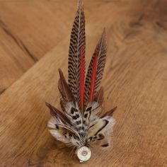 Created by talented Scottish artist Wendy Goode, on the Monymusk Estate in Rural Aberdeenshire. Inspired by the local wildlife and striking colours of pheasant feathers these spectacular brooches also use partridge, mallard, blue jay, guinea fowl and cockerel feathers. The vast majority of the feathers are sourced locally by the artist, and also feature donated feathers from other parts of the U.K.The bases for the feathers come from recycled cartridge and rifle shells sourced from local…