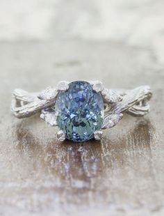 The Emery is simply exquisite in all her nature-inspired glory. She is created in shiny, bright 14k white gold. An amazing Oval cut Montana sapphire sits like a queen in the center of this band- set i