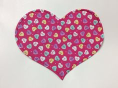 These set of four reversible heart shaped placemats are perfect for your Valentines Day decor. They are approximately 13 high x 16wide. Conversation hearts with sayings like: I luv you, text me, xoxo, u+ me, be mine, and call me.The reverse is a pink background with lighter pink hearts. Hand crafted of cotton fabric with a polyester fleece interfacing to provide a little bit of thickness as well as stability.Placemats can be washed and dried on cool temperatures. May be dried on a gentle…