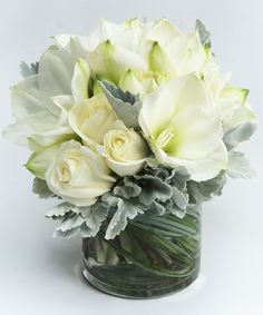 White Rose & Amaryllis Classic A timeless winter arrangement - this beautiful collection of white amaryllis and white roses is arranged in our signature cylinder vase.