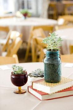 Some of the centerpieces will be clusters of vintage containers and vintage books with varied succulents, seasonal greenery and foliages and gray dusty miller.