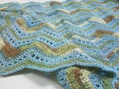 Playful Ripples Throw in blue. Free pattern from Red Heart. A mix of a one-colur yarn (blue) and a multi-colour yarn (greens and browns). I like it.