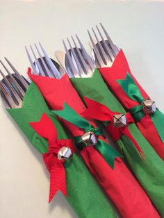 Disposable flatware wrapped in a green and red paper napkins (13 inches x 13 inches) with a ribbon napkin ring finished with a Christmas Bell.