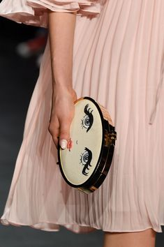 Clutch handbag with a 70's anime-inspired girls face with long lashes, by Erin Fetherston at New York Spring 2016