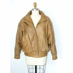 """Vintage Tan Leather Bomber Jacket ♡ MAKE ME AN OFFER! ♡ Questions? Please ask! Incredible tan brown leather vintage bomber jacket with zipper sleeve detail and elastic waistband in the back. Very good condition, with some """"lived in"""" signs of wear on the leather sleeves. Questions? Measurements? Modeling? Please ask!  + Size Medium + 100% Genuine Leather outer + 100% Nylon Taffeta lining Vintage Jackets & Coats"""