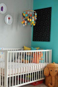chambre bébé en bleu canard un mur peint seulement avec des murs blancs et des tableaux décoratifs ronds coin haut en couleurs avec panier éléphant
