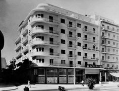 """1965, Αθήνα, Αμπελόκηποι - Λεωφ. Αλεξάνδρας Δίπλα στο γήπεδο του Παναθηναϊκού, που βρίσκεται αριστερά εκτός πλάνου. Η πολυκατοικία ήταν προφανώς νεόδμητη γιατί έχει ακόμη επιγραφή """"Πωλούνται διαμερίσματα"""". Στο ισόγειο ο κινηματογράφος """"Αρζεντίνα"""" (1963-1992). Σήμερα στεγάζει στούντιο ηχογράφησης. Αναρτήθηκε από τον Alexandros Papandreou στην ομάδα """"Οι Αμπελόκηποι της καρδιάς μας - Αμπελοκηπιώτικες αναμνήσεις"""" και προέρχεται από το αρχείο του Θεόδωρου Βαλμά."""